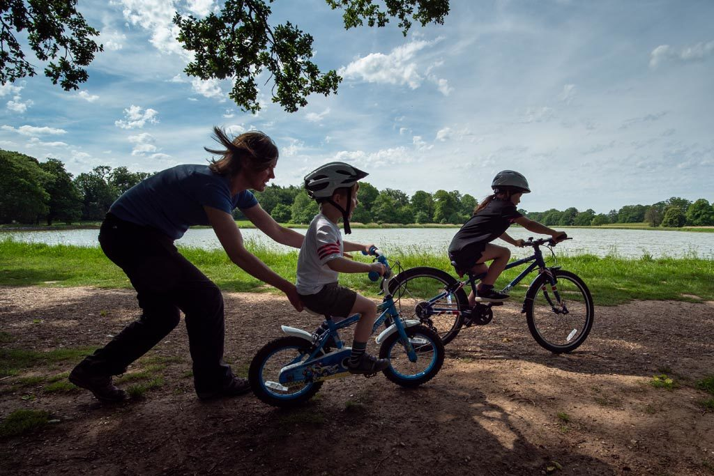 Family with bikes by the lake at Blickling Estate, Norfolk
